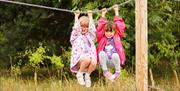 Two girls dangling from the playground chains at wolds way lavender, in East Yorkshire