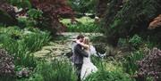 A bride and groom stood in the grounds of Saltmarshe Hall next to the pond in East Yorkshire.