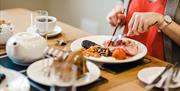 A lady eating a full English breakfast at Highfield Farm Bed & Breakfast, Driffield, East Yorkshire.