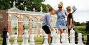 A  woman and two boys playing a game of giant chess in the grounds of Burton Constable Hall, Skirlaugh in East Yorkshire.