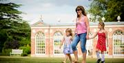 A woman and two young girls walking hand in hand through the grounds of Burton Constable Hall, Skirlaugh in East Yorkshire.