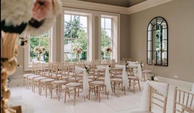 A room dressed for a wedding, complete with chairs and sashes, floral displays and large open windows/mirrors at Saltmarshe Hall, Goole in East Yorksh