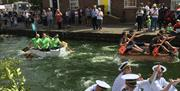 People racing along beverley beck in small rowing boats, complete with costumes for different teams and spectators along the bankside, in East Yorkshi