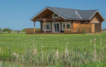 A large lodge with grassed surrounding at Lakeside Lodges in East Yorkshire.