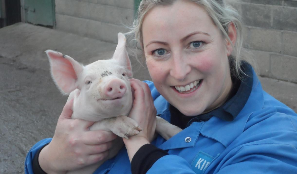 An image of a woman holding a small pig up at East Riding Country Pork Farm Shop.