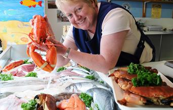 A lady displaying a fresh lobster above their seafood produce at Wingham's Fresh Fish in East Yorkshire.
