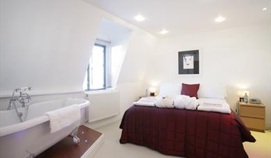 A double bed complete with feature bathtub in the bedroom at Carlton Apartments in East Yorkshire.