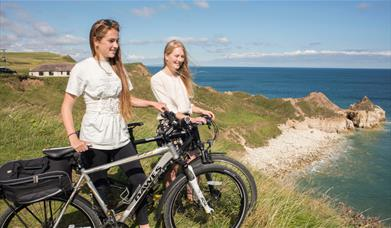 Two people with cycles near the cliff top at Flamborough in East Yorkshire.
