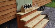 Wooden steps, firewood and some beer next to the Little Otchan Shepherds Hut in East Yorkshire.