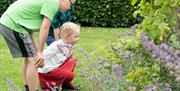 Children admiring the flowers at Scampston Hall and Walled Garden in East Yorkshire.
