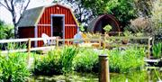 Glamping huts, lodges an pods sitting around the pond at Seaways Glamping and Camping in East Yorkshire.