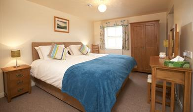 A double bedroom with blue throw at Highfield Farm in East Yorkshire.