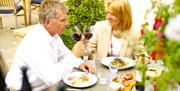 A man and woman, making a toast with their wine and enjoying a meal at Westwood Restaurant, in East Yorkshire