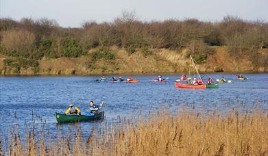 Some people enjoying rowing in canoes on a lake in East Yorkshire.