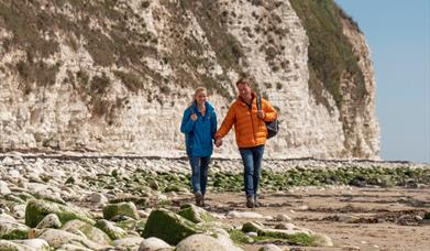 A couple walking along Bridlington South Beach in East Yorkshire.