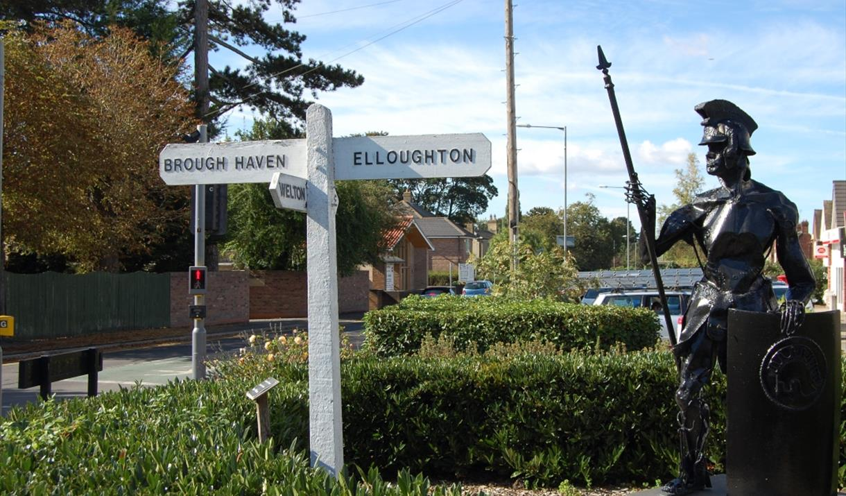 The sculpture of a centurion, and a fingerpost,  at Brough crossroads in East Yorkshire.