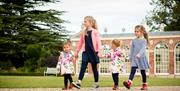 Four young girls walking hand in hand through the grounds of Burton Constable Hall, Skirlaugh in East Yorkshire.