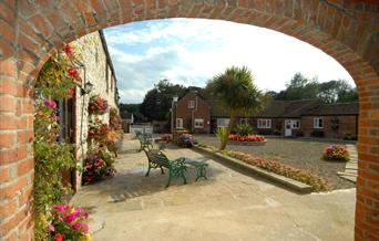 Looking through an archway onto an open area with seating at Grange Farm in East Yorkshire.