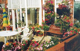 Lots of flowers with a table and chairs at the front of Spinnaker Guest House in East Yorkshire.