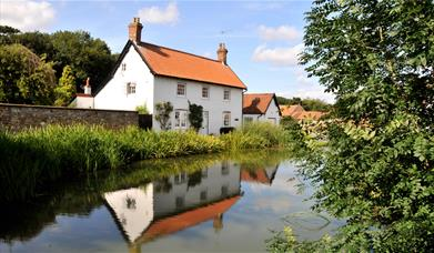 A cottage overlooking a river running through Bishop Burton, in East Yorkshire