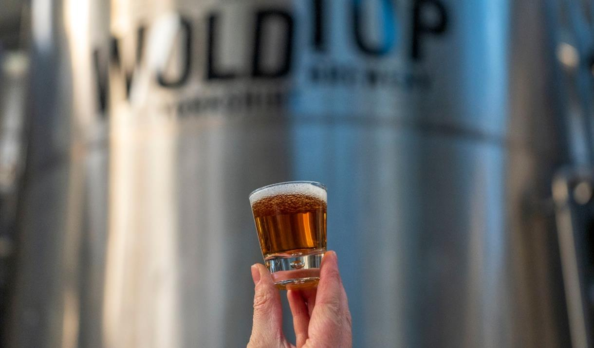 A person holding a glass of beer at Wold Top Brewery, Driffield in East Yorkshire.