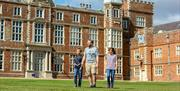 A man and two children walking through the grounds with Burton Constable Hall, Skirlaugh in East Yorkshire.