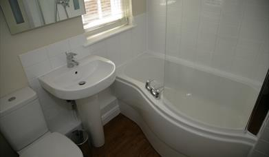 A bathroom with over bath shower at Sewerby Hall Cottages in East Yorkshire.