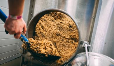 Someone scooping ingredients from a large drum at Atom Brewing Co, in East Yorkshire