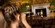 A girl looking through a telescope towards an open fire place at Burton Constable Hall, Skirlaugh in East Yorkshire.