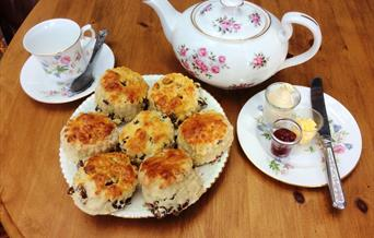 A traditional china teapot and teacups with a selection of scones at Rachel's Walnut Cottage Tearoom, in East Yorkshire