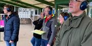 A group of visitors watching clay shooting, in East Yorkshire