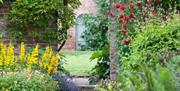 A small pathway leading you through the flowered gardens at Saltmarshe Hall in East Yorkshire.
