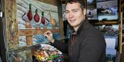 The artist stood with pallet in hand, painting an canvas of ducks at Robert Fuller Gallery, in East Yorkshire