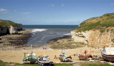 Overlooking the cove at north landing, including the cliffs, beach and cobble boats, in East Yorkshire