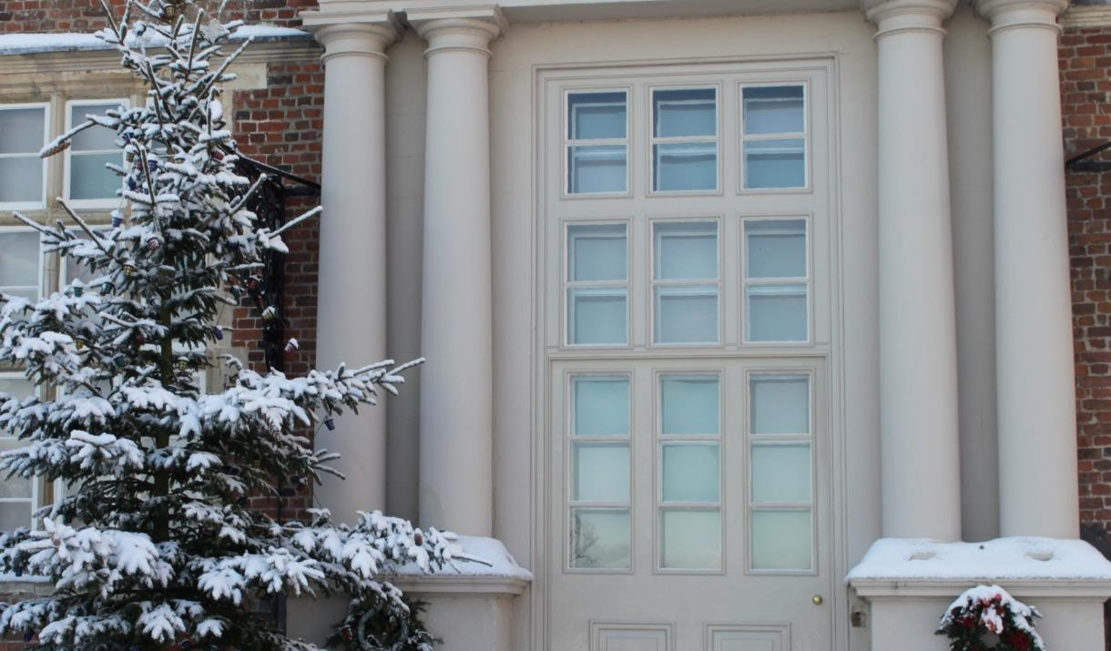 A snowy door, tree and wreath, at Burton Agnes Hall & Gardens in East Yorkshire.