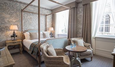 A four poster bed and seating area in a double room at The Beverley Arms in East Yorkshire.