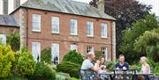Visitors sat eating in the gardens of Wold Cottage, East Yorkshire