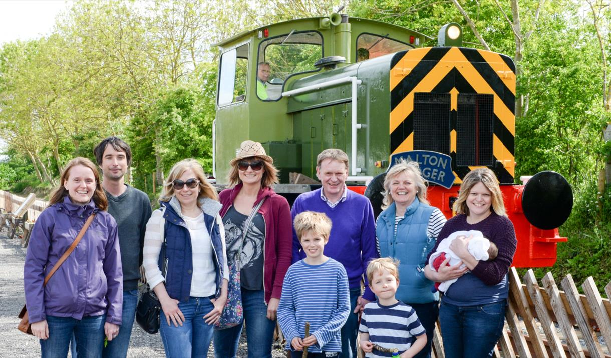 A group of people stood in front of a train at Yorkshire Wolds Railway, Driffield in East Yorkshire.