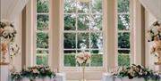 A picturesque window, dressed with floral displays for a wedding at Saltmarshe Hall, Goole in East Yorkshire.