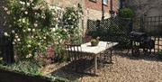 An image of the garden at Horseshoe Cottage, with table & chairs