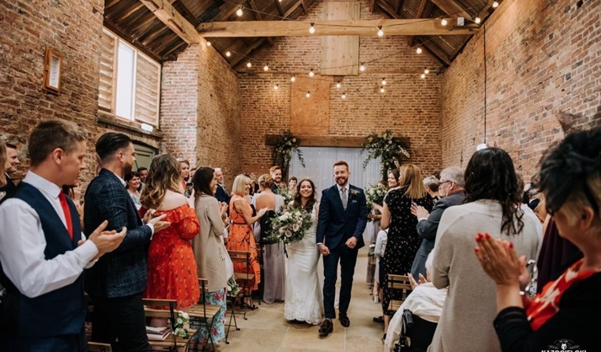 An image of a couple who have just got married at The Barns, with guests cheering & clapping.