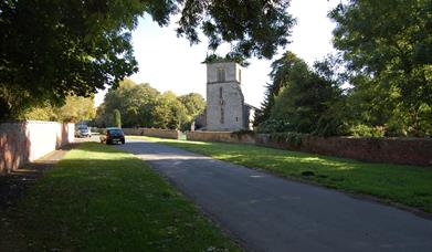 The main road with the church in the distance at Londesborough, East Yorkshire.