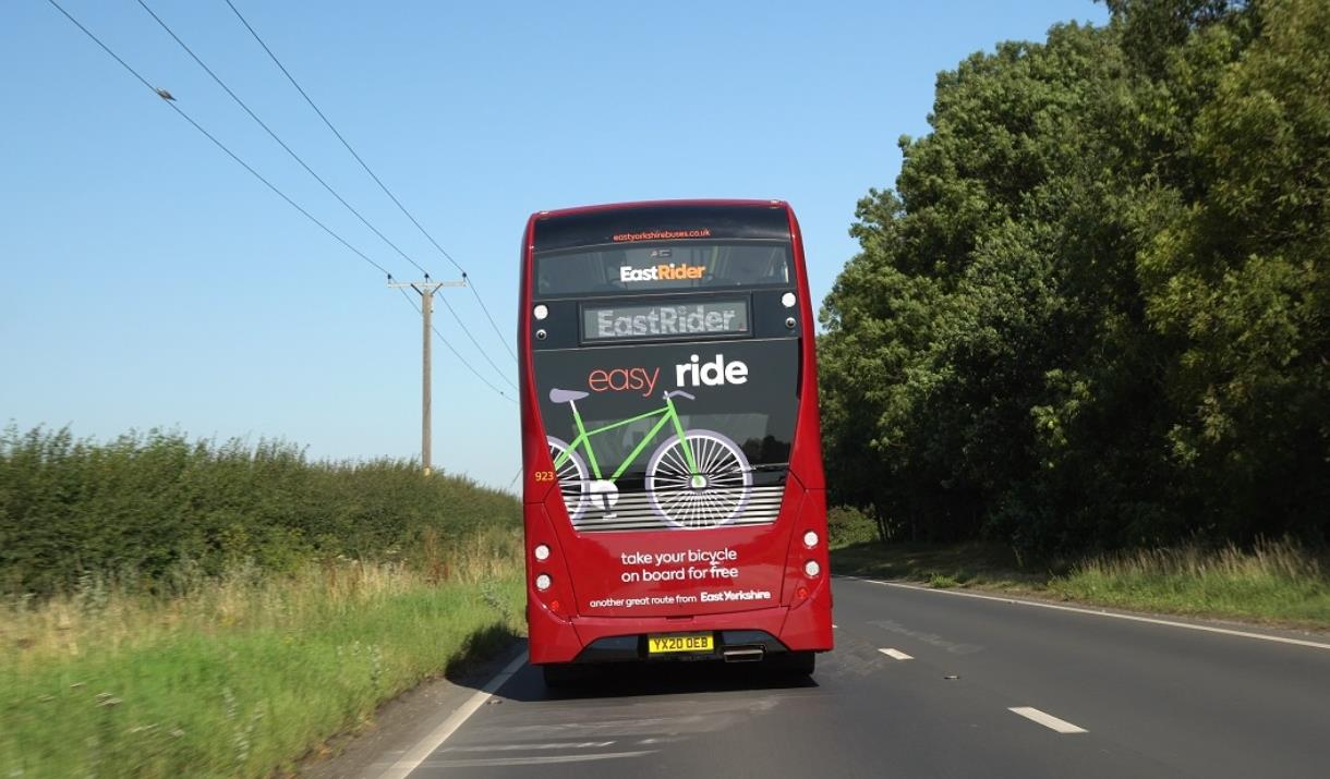 The rear of an East Yorkshire bus with a bike friendly advert on it, travelling through the countryside, in East Yorkshire