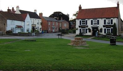 The centenary bench on the village green and The Gnu pub in the background at North Newbald, East Yorshire