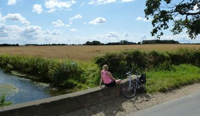 A woman sitting on a bridge, enjoying the view, with her bike leant against the bridge next to her, in East Yorkshire