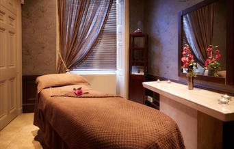 A spa room, with cosy blanket on the massage couch & candles lit at The Sessions Hair, Health and Beauty Spa, Beverley in East Yorkshire.