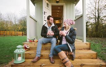 A couple sitting on the steps of a shepherd's hut at Snug Huts in East Yorkshire