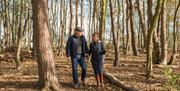 A couple enjoying an autumn walk in the woodland at South Cliff Holiday Park, Bridlington, East Yorkshire