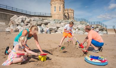 A family making sandcastles on the beach in front of Pier Towers at Withernsea, in East Yorkshire.