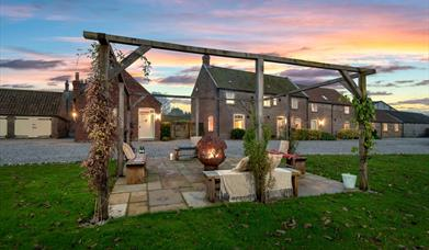 The outdoor seating area including firepit, taken at sunset at Broadgate Farm Cottages, Walkington, East Yorkshire.